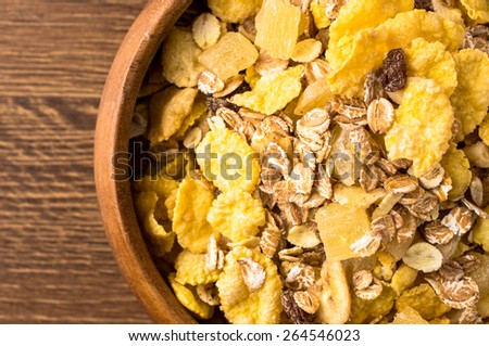 Breakfast cereals in wooden bowl closeup view from above - stock photo