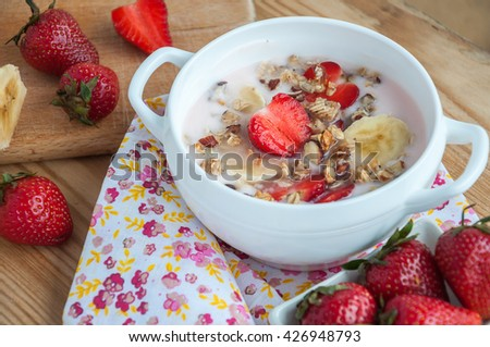 breakfast consisting of vanilla greek yogurt topped with granola, sliced bananas and strawberries, on an old wooden textured table with flower fabric - stock photo