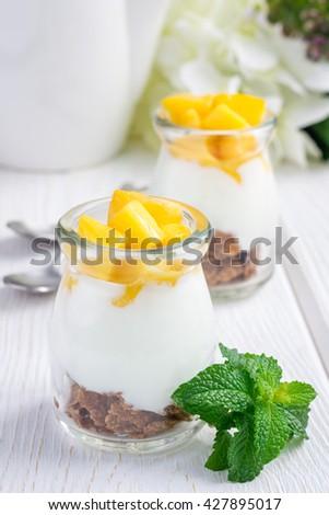 Breakfast dessert with bran flakes, plain yogurt and mango, on a wooden table - stock photo