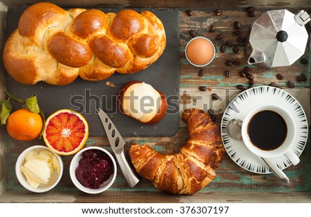 Breakfast flat lay of freshly baked bread, croissant, pretzel roll along with fruit, boiled egg and coffee. All served on a rustic wooden tray table. - stock photo