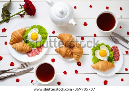 Breakfast for couple on Valentines day with heart shaped fried eggs, salad, croissants, salami sausage, rose petals composition and tea - stock photo