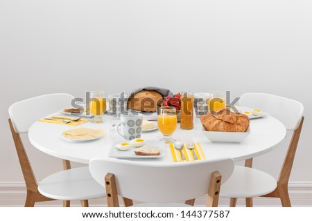 Breakfast for three. Simple tasty morning meal on a white table. - stock photo