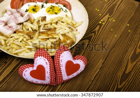 Breakfast for two on Valentine's Day. Frying pan with a meal and two hearts. On wooden background. - stock photo