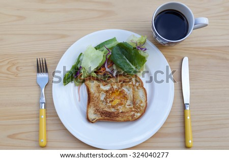 Breakfast fried egg on toast and green salad with cup of coffee - stock photo