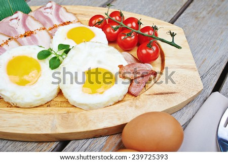 Breakfast - fried egg with bacon and vegetables on the wooden plate - stock photo