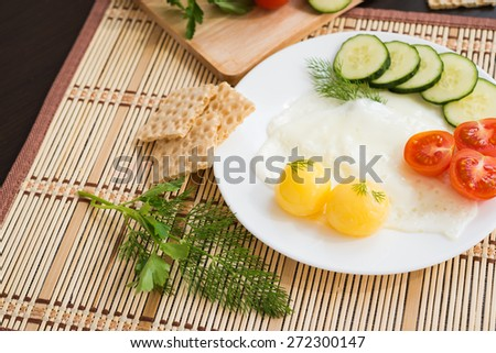Breakfast - fried eggs (with a raw egg yolk) and vegetables - stock photo