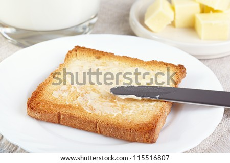 Breakfast. Glass with milk and toasts with butter - stock photo