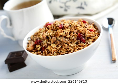 Breakfast: homemade granola with almonds and dried cranberries in white bowl. Two pieces of dark chocolate and cup of green tea on side - stock photo
