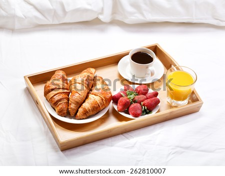 breakfast in bed with coffee, croissants, strawberries and juice - stock photo