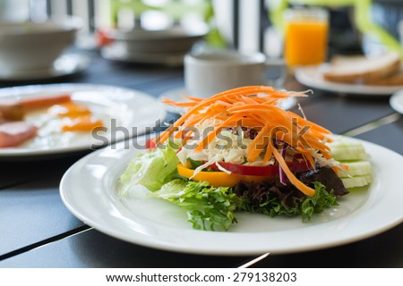 Breakfast is served with salad, fried egg, ham, orange juice and delicious. - stock photo