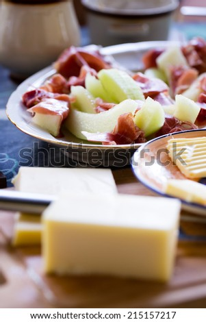 Breakfast - melon and prosciutto ham with butter in natural light  - stock photo
