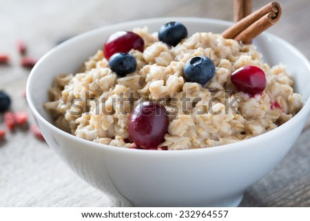 Breakfast oatmeal porridge with cinnamon, cranberries and blueberries, front view, selective focus - stock photo