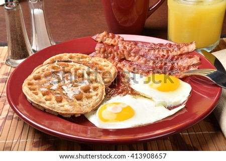 Breakfast of bacon and fried eggs with multi grain waffles - stock photo