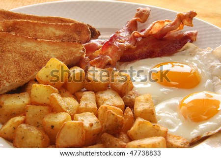 Breakfast of eggs, bacon, toast and hash browns. Also available with sausage instead of bacon. - stock photo