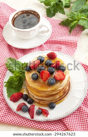 Breakfast of pancakes on  ceramic plate and tea cup - stock photo