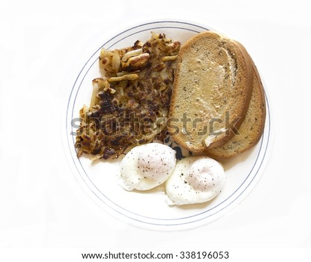 Breakfast of poached eggs, hash browns and rye toast. - stock photo