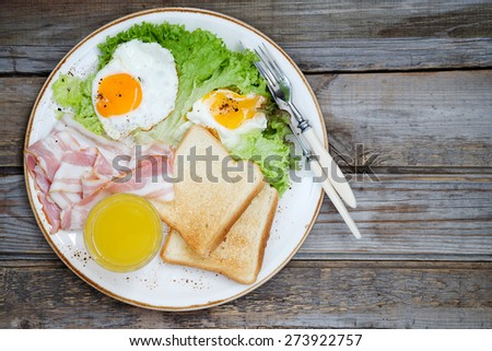 Breakfast on a plate: fried eggs, bacon and lettuce. Top view, copy space - stock photo
