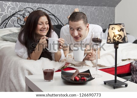 Breakfast on a table with couple lying in background at resort - stock photo