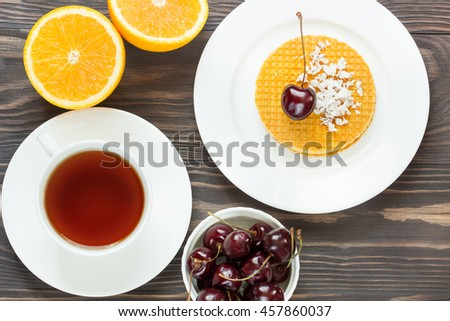 Breakfast on a wooden table with waffles and fresh berries - stock photo