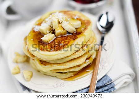 Breakfast: pancakes with banana, coconut flakes and honey on plate - stock photo