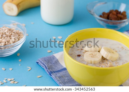 Breakfast porridge with bananas and raisins - stock photo