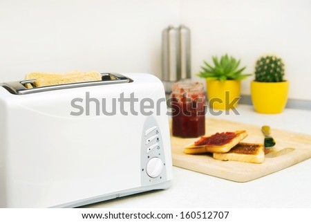 Breakfast prepare. Toaster and toast with jam in modern kitchen - stock photo