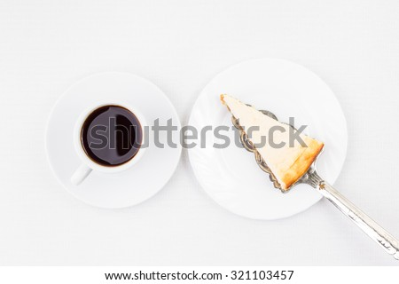 Breakfast restaurant menu background. Wedge of Cheesecake on the spatula and cup of coffee on white table. Top view image - stock photo