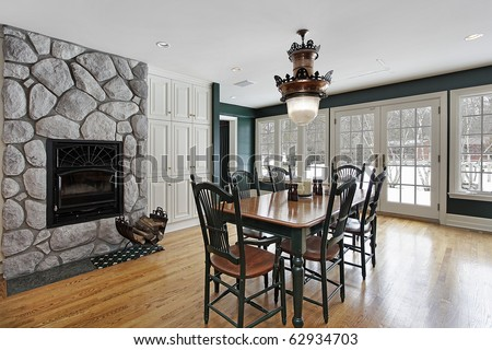 Breakfast room in luxury home with stone fireplace - stock photo