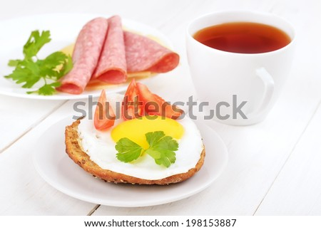 Breakfast - sandwich with fried egg, tomato slices and tea on wooden table - stock photo