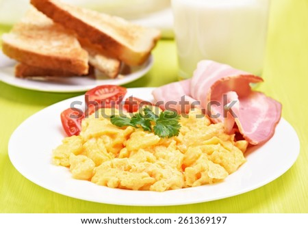Breakfast scrambled eggs with bacon and tomatoes on white plate, close up view - stock photo
