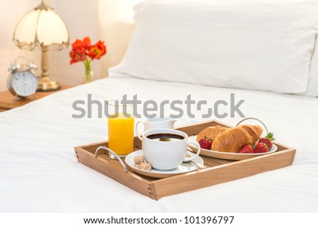 Breakfast served in bed on wooden tray with coffee and croissants - stock photo