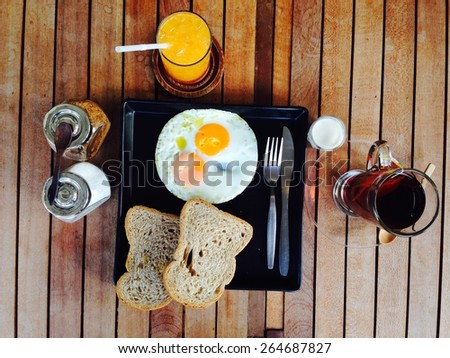 Breakfast set, fried eggs, toast, orange juice, milk and tea.  - stock photo