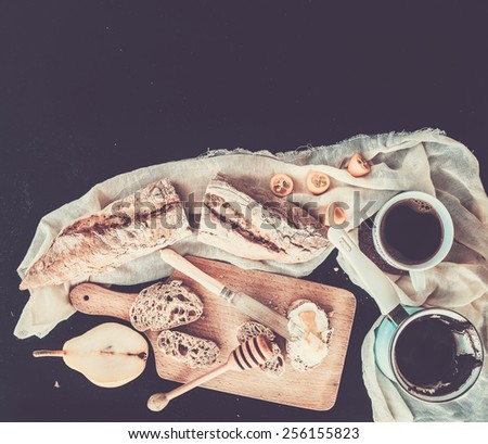 Breakfast set. Pot or cezve of coffee, a cup on a kitchen towel, kumquats, pears, baguette slices with butter cream and honey on a rustic wooden board over a black backdrop with a copy space. Top view - stock photo