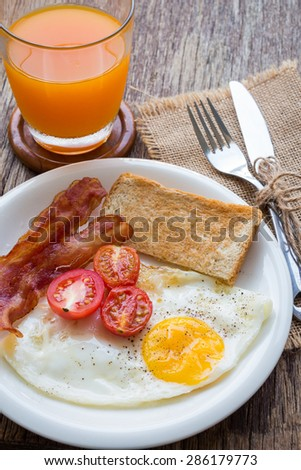 Breakfast set with bacon, eggs and toasts on wooden table, rustic style. - stock photo