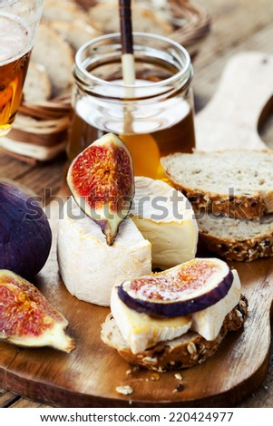 Breakfast setting with bread, cheese, figs and honey - stock photo