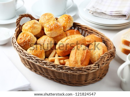 Breakfast table with basket and bread rolls - stock photo