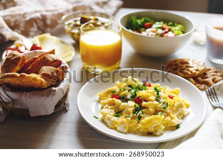 Breakfast Table with Scrambled Eggs, Fresh Bread, Orange Juice in Morning Sun at Home. Selective focus. - stock photo
