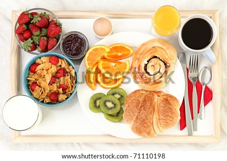 Breakfast tray in bed with coffee, bread, cereals, fruit etc. - stock photo