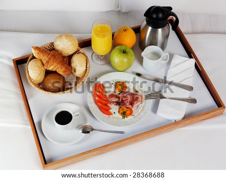 Breakfast tray laying on white bed in upscale hotel - stock photo