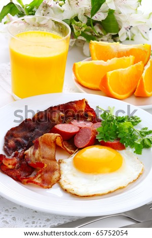 Breakfast with bacon, fried egg and orange juice - stock photo
