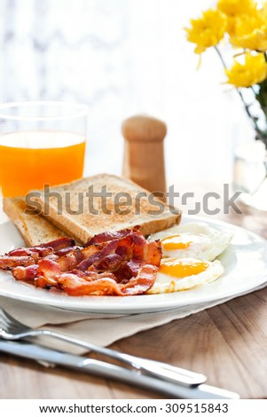 breakfast with bacon,fried egg,bread and orange juice - stock photo