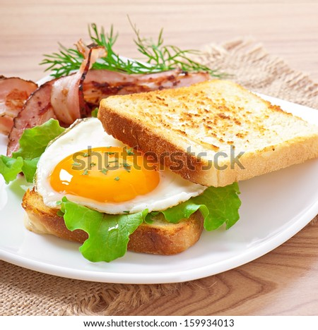 breakfast with bread, fried egg and bacon - stock photo