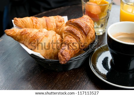 Breakfast with coffee and croissants in a basket on table - stock photo