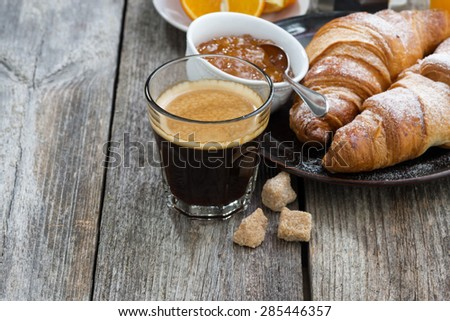 breakfast with croissants, espresso and orange jam on wooden background, horizontal - stock photo