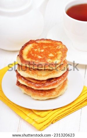Breakfast with curd pancakes and tea on white wooden table - stock photo