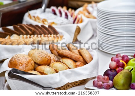 Breakfast with different kinds of breads and fruits - stock photo