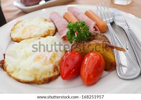 breakfast with egg, ham, hot dog, sweet potato and tomato - stock photo