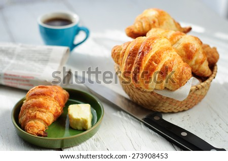Breakfast with fresh baked croissants, butter and coffee on white wooden background, newspaper - stock photo