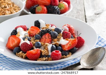 breakfast with fresh berries, yogurt and homemade granola, close-up - stock photo