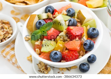 breakfast with fruit salad and corn flakes, closeup top view, horizontal - stock photo